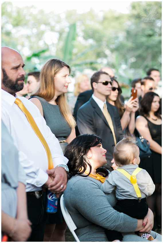 Wedding guests look on as the couple recite their vows.
