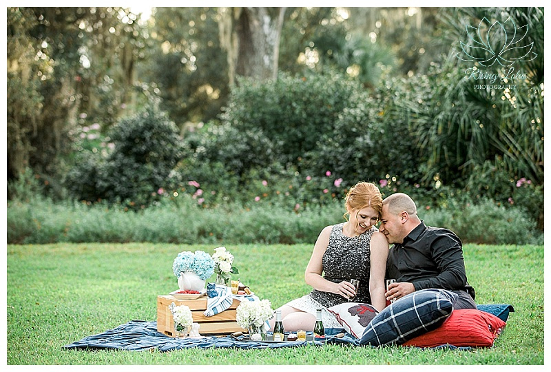Engaged couple enjoy a champagne toast and a picnic during their engagement session at Bok Tower.