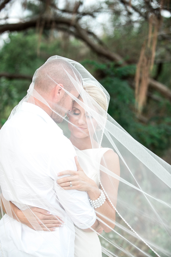 Newlyweds embrace beneath the bride's veil during a bridal session at Fort De Soto beach