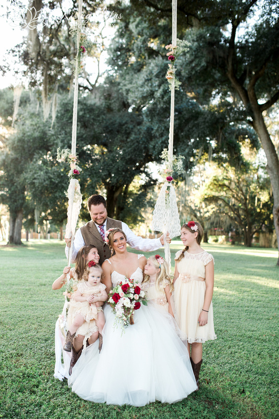 The newlyweds and their flower girls together on a swing at Casa Lantana.