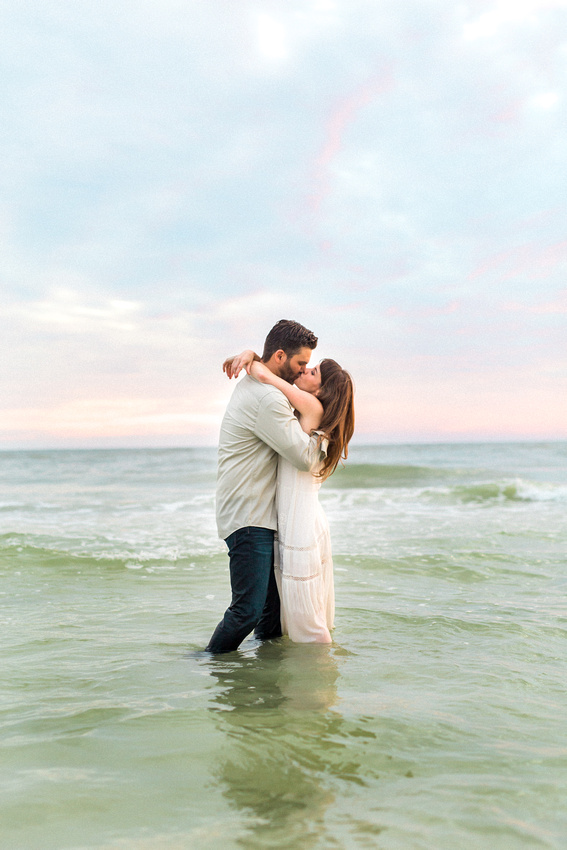 Emily and Chris kiss while standing in the ocean at Longboat Key