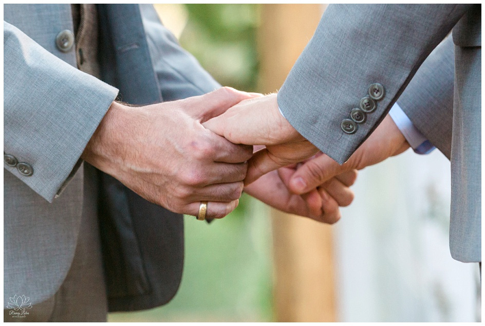 Same sex couple hold hands during the recital of their wedding vows.