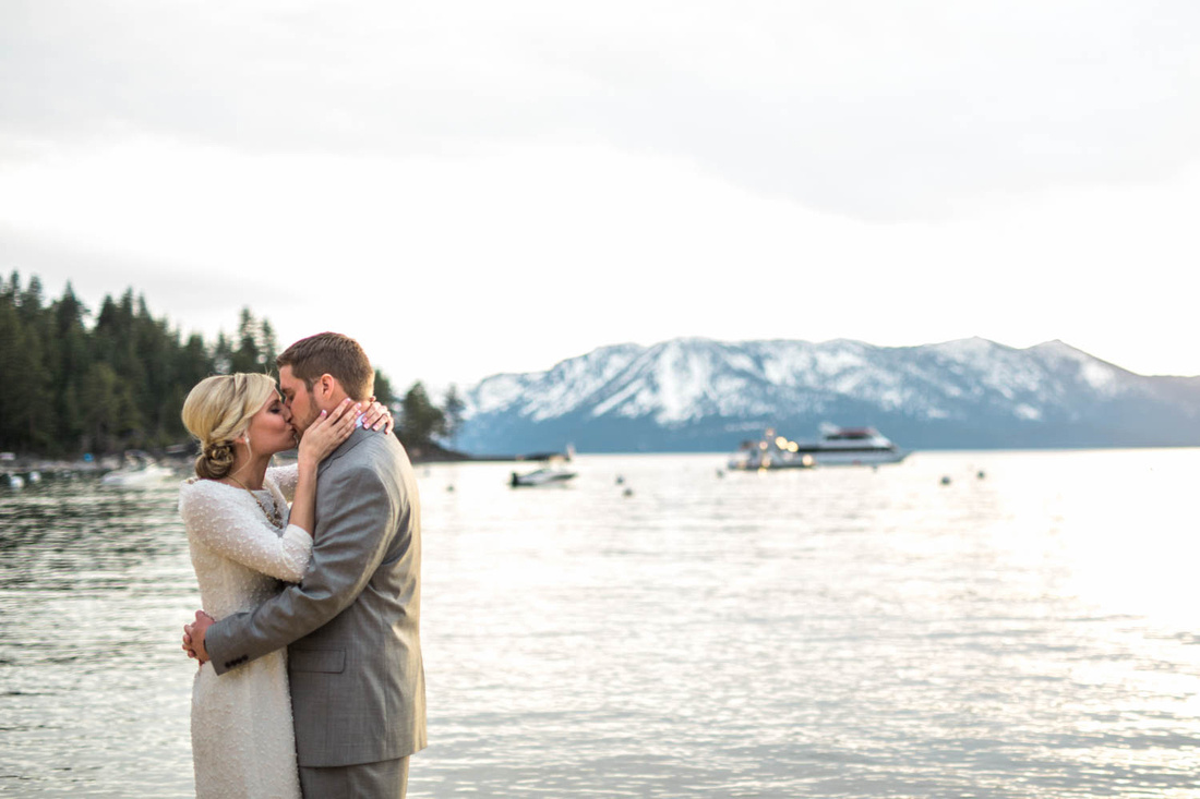 Alissa and Jeremy kiss near the pier at Zephyr Cove during their engagement session with Rising Lotus Photography.