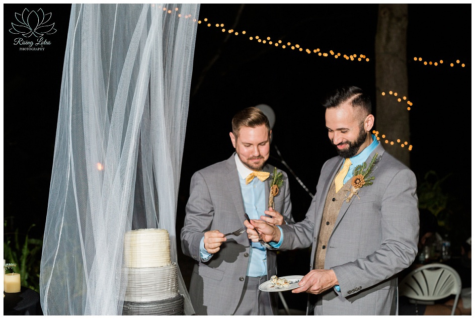 Same sex couple enjoy their first bites of wedding cake during their wedding reception.
