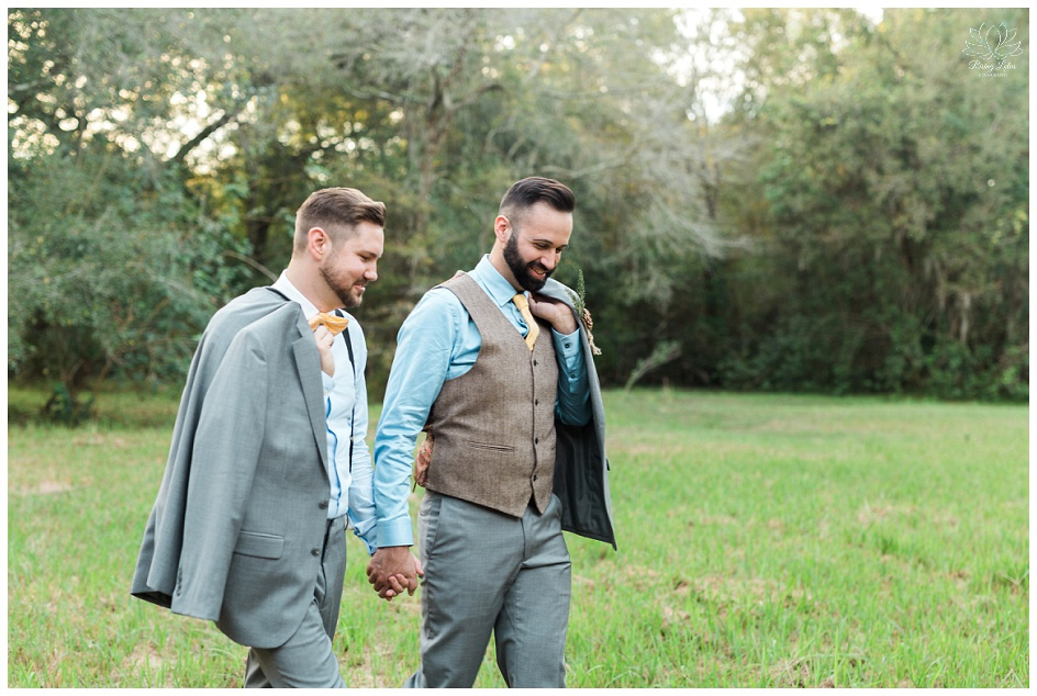 The grooms walk back to their wedding reception after taking photos.