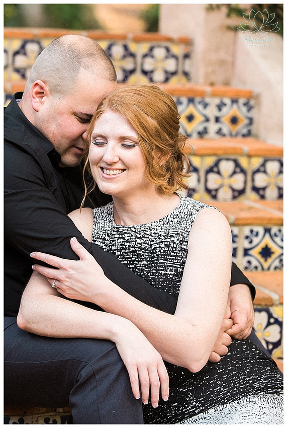 Amanda and Jose snuggle on the steps of the Pinewood Estate at Bok Tower by Rising Lotus Photography.