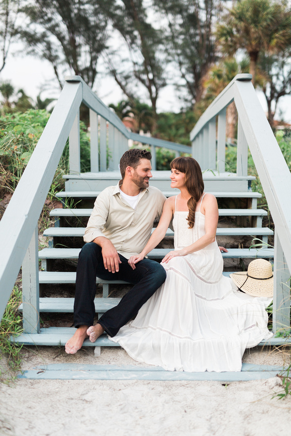 Emily and Chris sit on the boardwalk during their engagement session at Longboat Key.