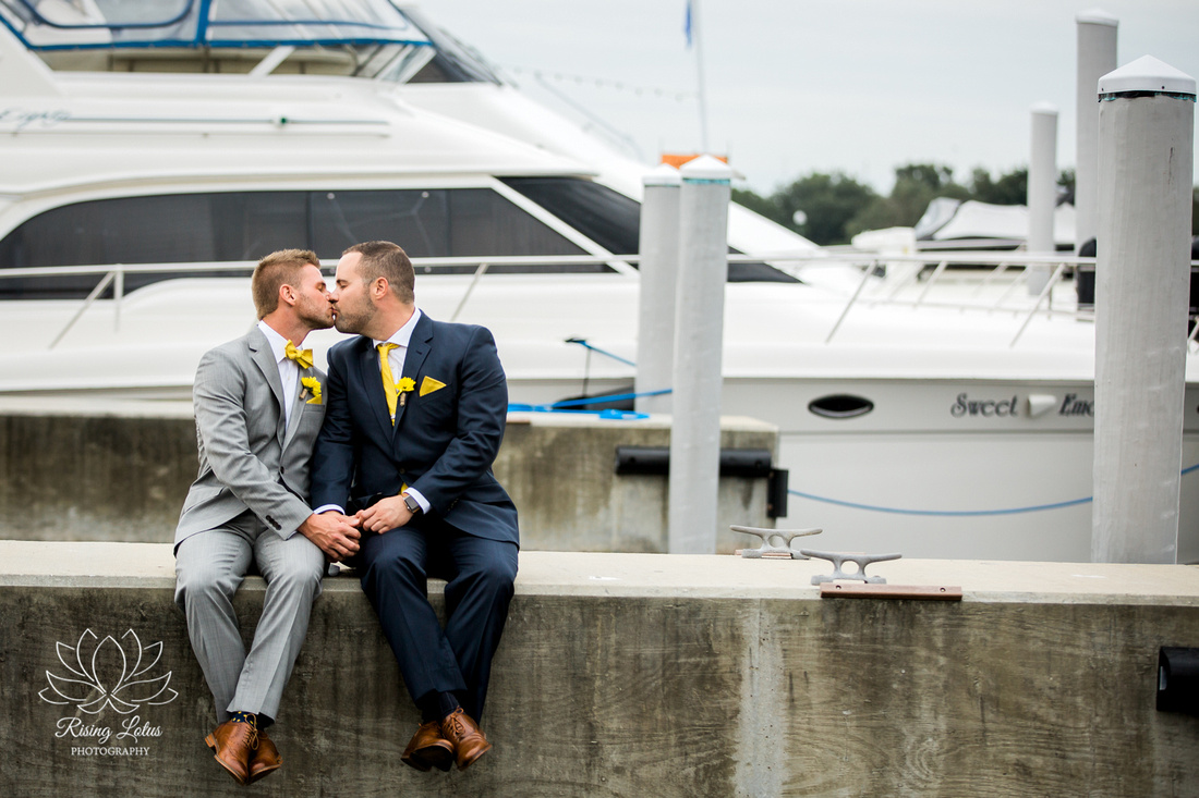 The grooms share a kiss along the St. Petersburg marina before their wedding ceremony aboard the Starship Yacht.