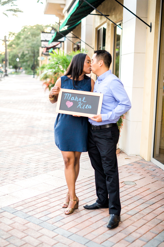 Engaged couple kissing and holding mahal kita chalkboard sign.