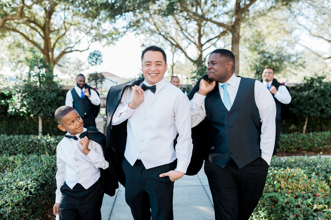 A groom pauses for photos with his best man and the ring bearer in the Palmetto Club's garden.