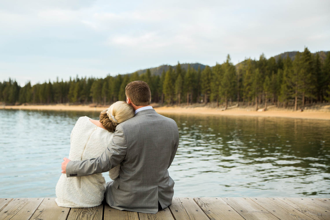 Engaged couple sit on the pier and have a sweet moment during the Lake Tahoe engagement session.